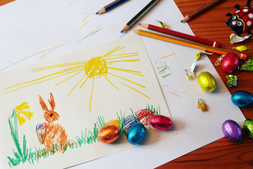 drawing of the Easter bunny, chocolate eggs and colored pencils