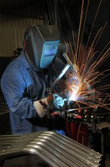 Welder welding a metal part in an industrial factory