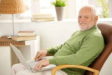 Portrait of aged man with laptop