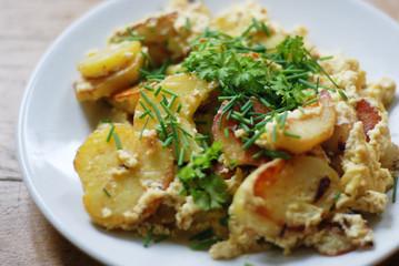 Rösti auf Teller mit Ei und Grün