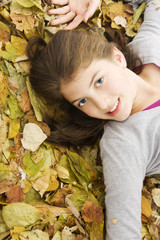 Portrait of teenage girl lying down with leaves around.