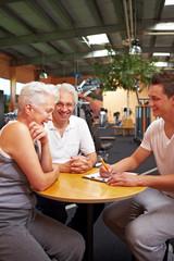 Senioren im Gespräch mit Fitnesstrainer