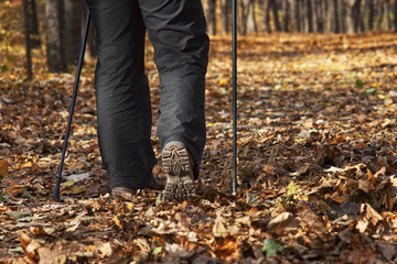 Closeup of shoe sole with Nordic walk sticks in autumn forest