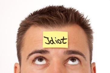 Mann mit Haftnotiz auf der Stirn - Idiot