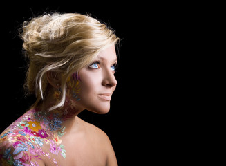 portrait of beautiful girl with floral theme bodyart on black ba