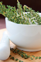 Mortar and pestle with herbs on a wooden board