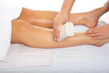 Beautician waxing woman leg