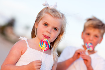 Precious Little Girl and Her Brother Enjoying Lollipops
