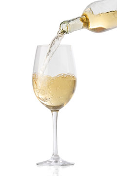 Pouring white wine into a glass, isolated on white background