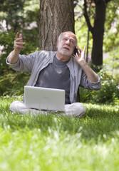 senior retraité avec téléphone ordinateur media
