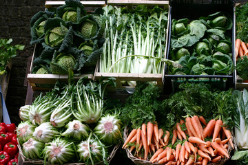 green vegetables and carrots on a market stall