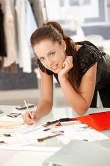 Attractive fashion designer working in office