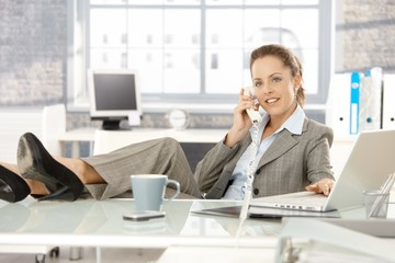 Young businesswoman talking on phone in office