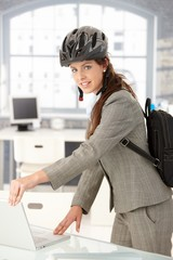 Young businesswoman leaving office by bike smiling