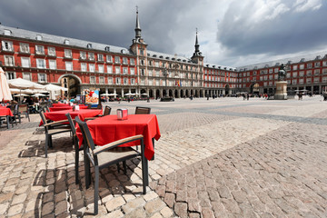Cafe tables with red tableclothes in Plaza Mayor. Madrid.