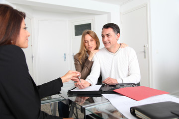 Couple signing property contract with real estate agent