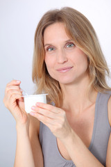 Closeup of beautiful woman eating yogurt