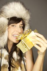 Frau öffnet die Schleife mit den Zähnen