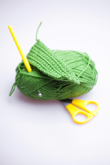 skein of wool with scissors and crochet hooks on a gray backgrou