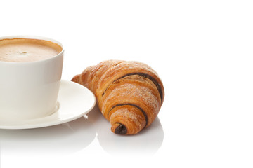 Cup of coffee and chocolate croissant on white background