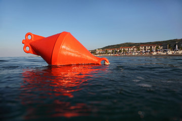 anchor buoy floats on sea. beach could be seen in distance