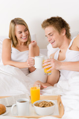 Luxury hotel honeymoon breakfast - couple in bed