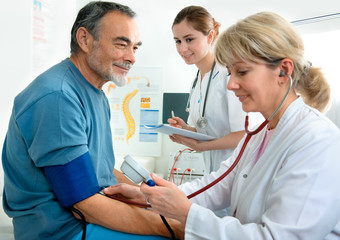 Patient is being observed by doctor - measuring blood pressure