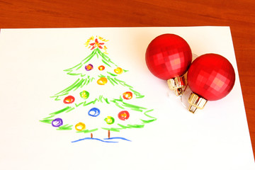Child's drawing and christmas balls on the table
