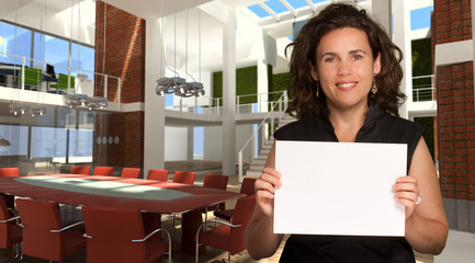 Woman in magnificent office holding a blank sign