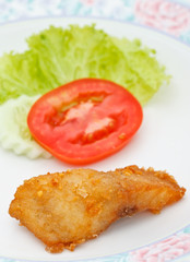 Piece of fried fish and vegetables