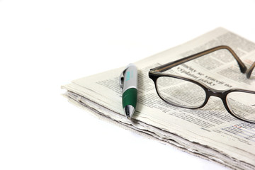 Newspaper with glasses and pen