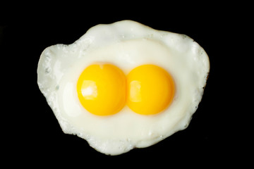 Fried two-yolks egg on black background