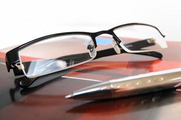 Magazin mit Brille und Kugelschreiber