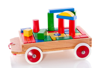 colorful wooden toy bocks in a car isolated over white