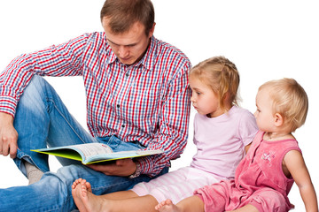 Father reading a book to his children