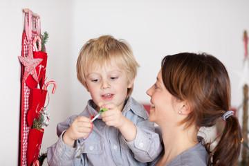mutter mit glücklichem kind vor dem weihnachtsgeschenk