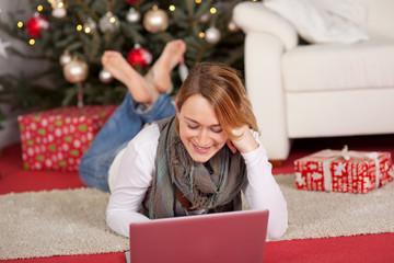 frau mit laptop vor dem weihnachtsbaum