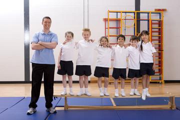 Smiling gym teacher and school children in school gymnasium