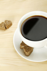 Closeup of a white cup of coffee next to lay pieces of sugar