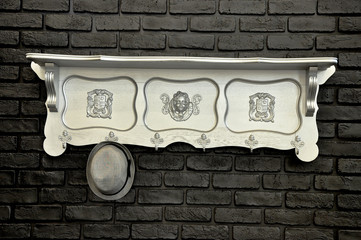 Vintage wooden silver rack with a hat on the black brick wall