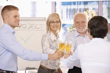 Businessteam clinking champagne glasses