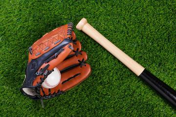 Baseball glove bat and ball on grass