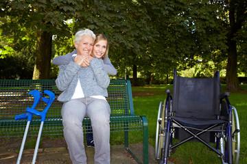 Frau umarmt Seniorin auf Parkbank