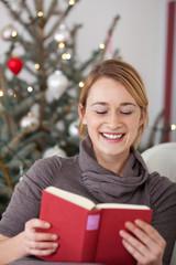 frau liest buch an weihnachten