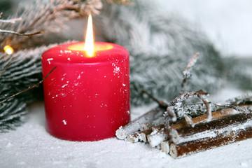 candela rossa in composizione natalizia