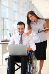 Businessman in wheelchair with assistant in office