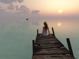 woman sitting on pier at sunrise