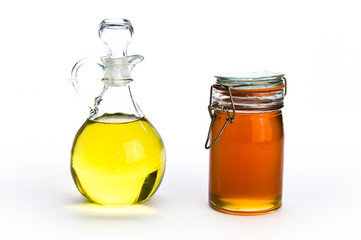 Fancy glass containers of oil and honey on isolating background