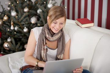frau mit computer vor dem weihnachtsbaum