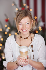 junge frau mit kaffee vor dem weihnachtsbaum
